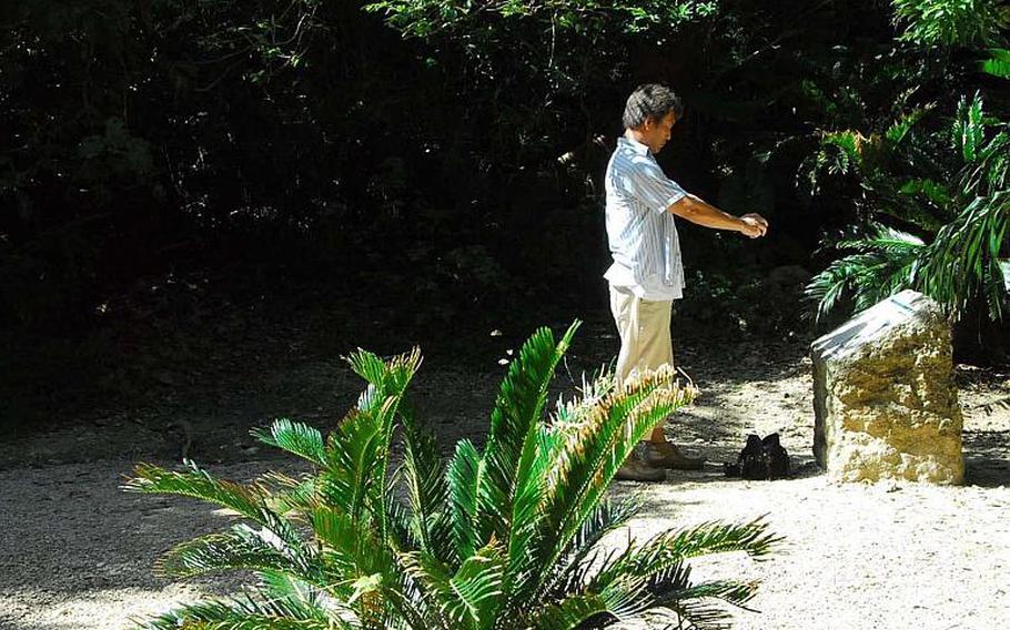 A visitor photographs an historic plaque in the prayer garden of the Sefa Utaki holy site.