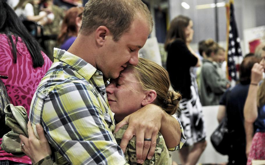 Spc. Jessie Nelson, 4th Brigade, 2nd Infantry Division (Stryker), hugs her husband, Matt, at Soldiers Field House on Joint Base Lewis-McChord, Wash. Nelson and approximately 230 other soldiers returned home after an eight-month deployment to Afghanistan.