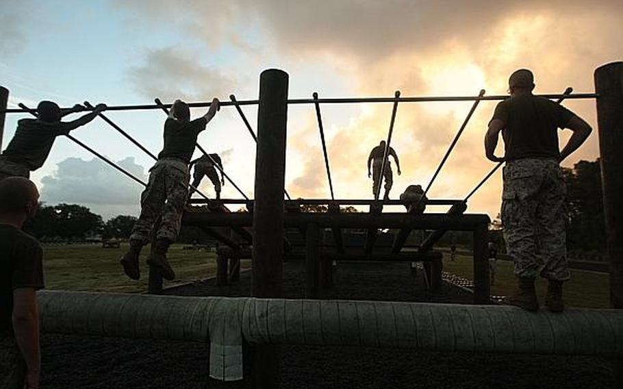 Recruits of Company I, 3rd Recruit Training Battalion, swing across parallel bars on an obstacle course Aug. 19, 2013, on Parris Island, S.C.