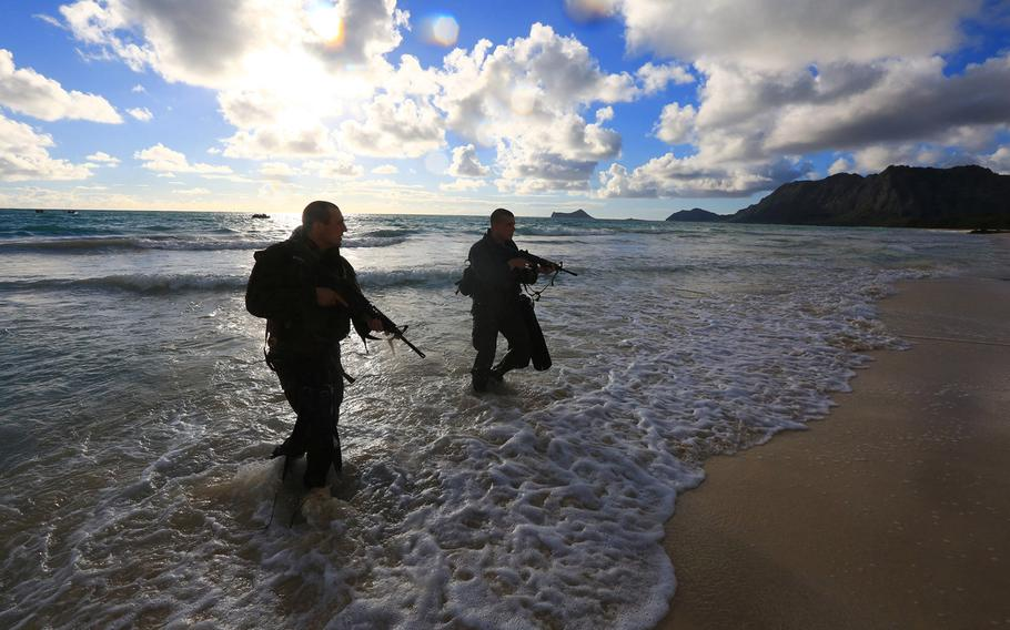 Two reconnaissance Marines with Battalion Landing Team 1/4, 13th Marine Expeditionary Unit, emerge from the water at Bellows Beach on the Island of Oahu, Hawaii, during training Aug. 30, 2013.