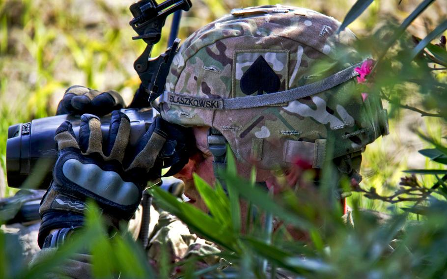 U.S. Army Staff Sgt. Eric J. Blaszkowski uses binoculars to scan the surrounding area to look for potential enemy movement during a mission in the Saberi district in Afghanistan's Khowst province, Aug. 27, 2013.