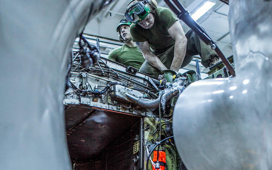 Cpl. Garret J. Madson, left, from Henderson, La., and Cpl. Josh L. Loudermeck, from Taylorsville, N.C., both airframe mechanics with Marine Medium Tiltrotor Squadron 265 (Reinforced), 31st Marine Expeditionary Unit, take out the engine of an AV-8B Harrier II jet inside the hangar bay aboard the USS Bonhomme Richard on Sept. 6, 2013.