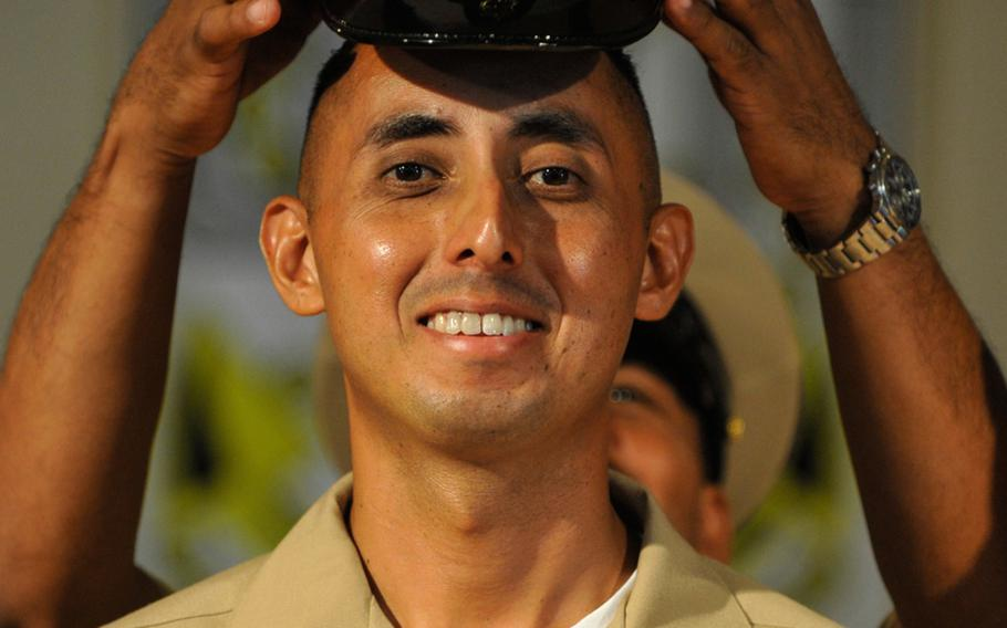 Chief Petty Officer Gabriel Martinez, a boatswain's mate, has his new cover place on his head during a chief petty officer pinning ceremony at Camp Lemonnier, Djibouti. Navy commands world-wide pinned about 4,600 sailors selected for E-7 last week to the rank of a chief petty officer.