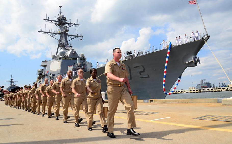 """Chief selectees from USS Mahan sing """"Anchors Away"""" as they march to their pinning ceremony held at the end of the pier in Norfolk, Va., on Sept. 13, 2013 ."""