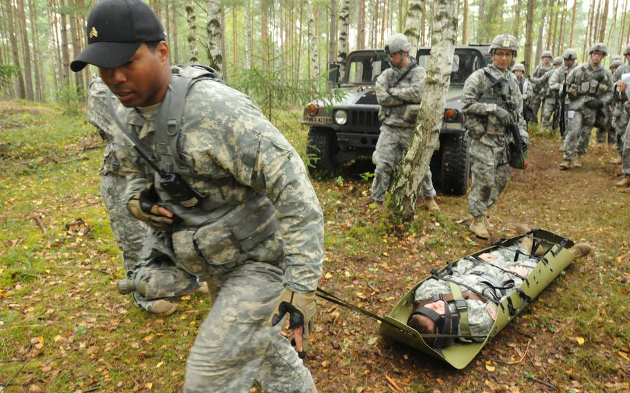 Sgt. Willard Wilson, a member of the U.S. Army's Bavaria Dental Activity, demonstrates how to pull a casualty on a rescue stretcher on Sept. 11, 2013, for candidates hoping to earn the Army Expert Field Medical Badge at Grafenwöhr Training Area in Germany.