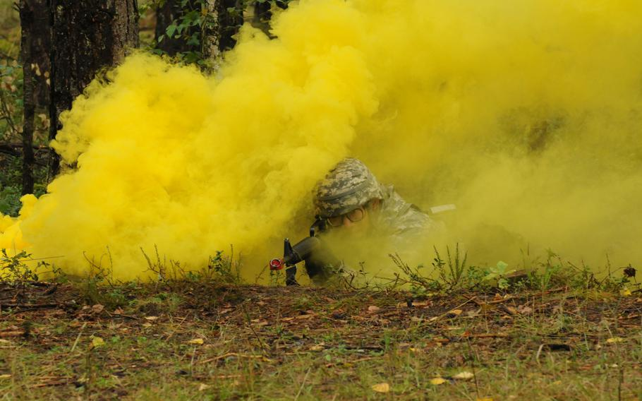 Partly concealed by smoke from a smoke grenade, Army 2nd Lt. Chunjiang Liao of the 21st Theater Sustainment Command's 16th Sustainment Brigade lies in the prone firing position Sept. 13, 2013, during testing for the Expert Field Medical Badge at Grafenwöhr, Germany.