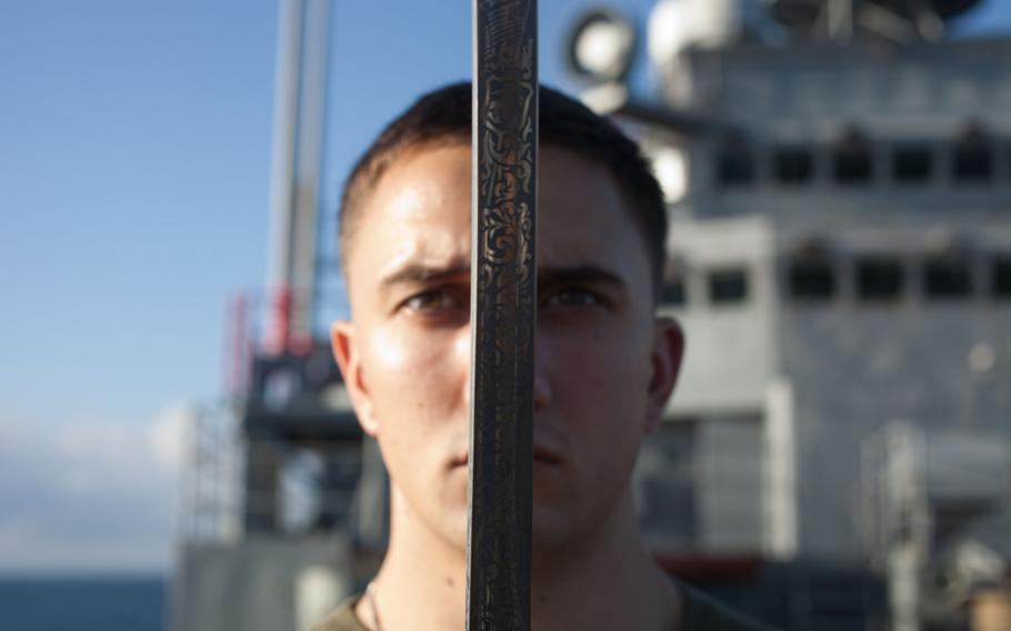 Cpl. Jacob A. Flury, with the 31st Marine Expeditionary Unit, executes a movement with a noncommissioned officer sword during a Corporals Course class on the bow of the USS Denver, Sept.14, 2013.