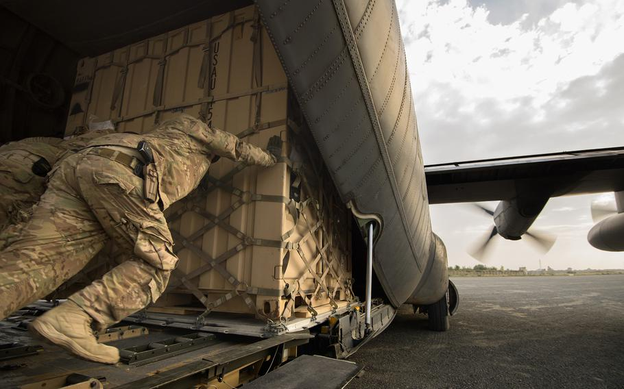 Staff Sgt. Daniel Hall, along with other 19th Movement Control Team aerial porters muscle a shipping container into a 774th Expeditionary Airlift Squadron C-130 Hercules cargo plane at Forward Operating Base Salerno, Khost province, Afghanistan, Sept. 22, 2013.