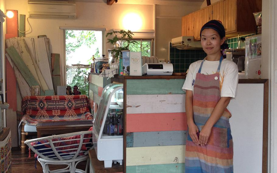 Mikie Takahashi, proprietor for the Mellow Food Cafe, stands next to some colorful wood siding, an original element recycled from old U.S. military family housing on Johnson Air Base. Takahashi, pictured Oct. 10, runs her business inside Johnson Town, a co-op outside Iruma Air Base in Saitama, Japan.