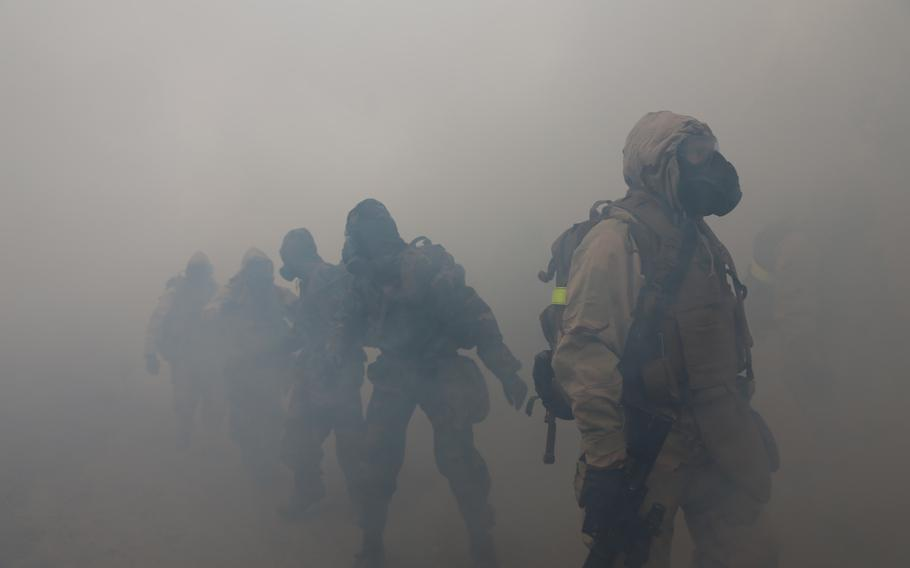 Marines with the 11th Marine Expeditionary Unit move through tear gas during a hike here on Oct 25, 2103.