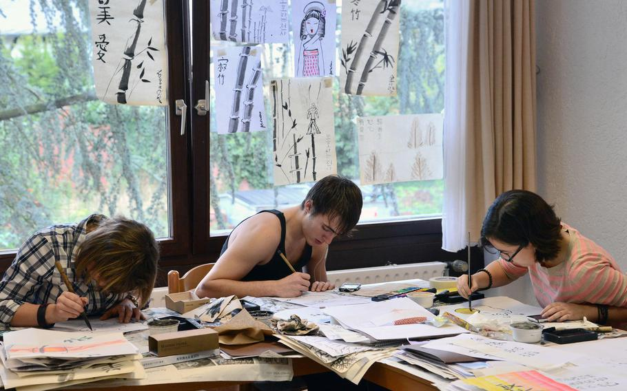 In the calligraphy workshop at Creative Connections, Vicenza's Alexandra Bass, Aviano's Levi Robertson and Lauren O'Brien of Naples work on their pieces. Finished works hang on the window behind them.  More than 160 students from DODDS-Europe high schools participated in this year's event that features 11 workshops in the visual and performing arts.