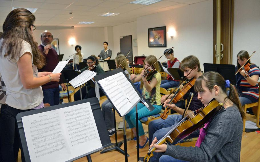 """Under the direction of Cary Sand, second from left, the strings workshop practices Coldplay's """"Viva La Vida"""" at this year's Creative Connections. More than 160 students from DODDS-Europe high schools participated in this year's event that features 11 workshops in the visual and performing arts."""