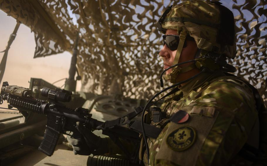 """Sgt. Charles Smith with 3rd Squadron, 2nd Cavalry Regiment pulls """"air guard"""" from a hatch in the back of a Stryker during a recent partnered patrol with the Afghan police of a village north of Forward Operating Base Pasab in southern Afghanistan's Kandahar province on Oct. 21, 2013."""
