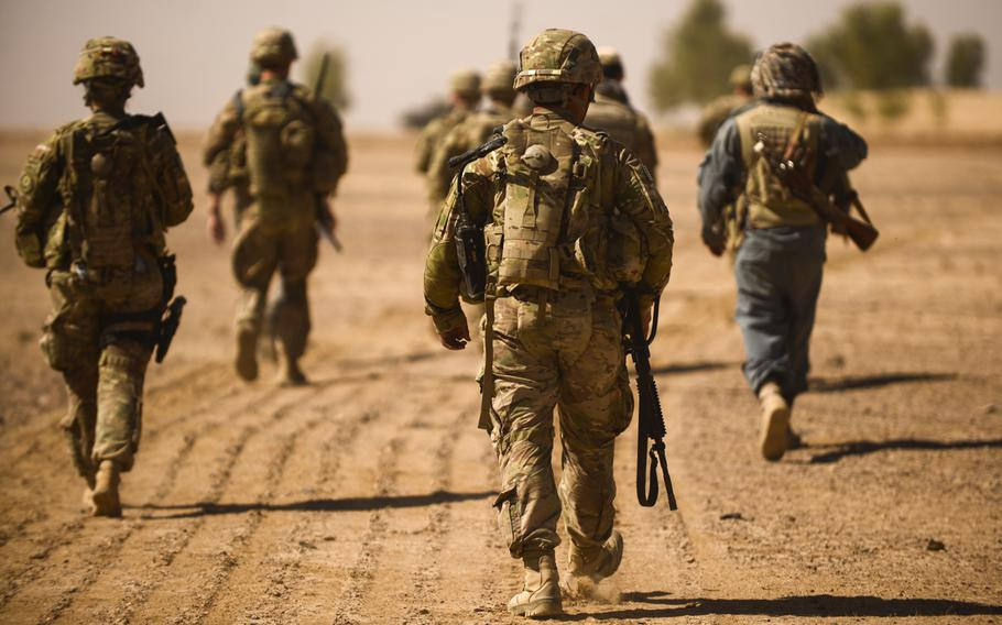 Soldiers with the 2nd Cavalry Regiment and the 163rd Military Intelligence Battalion conduct a partnered patrol with Afghan police in the desert of southern Afghanistan's Kandahar province just north of Forward Operating Base Pasab on Oct. 21, 2013.