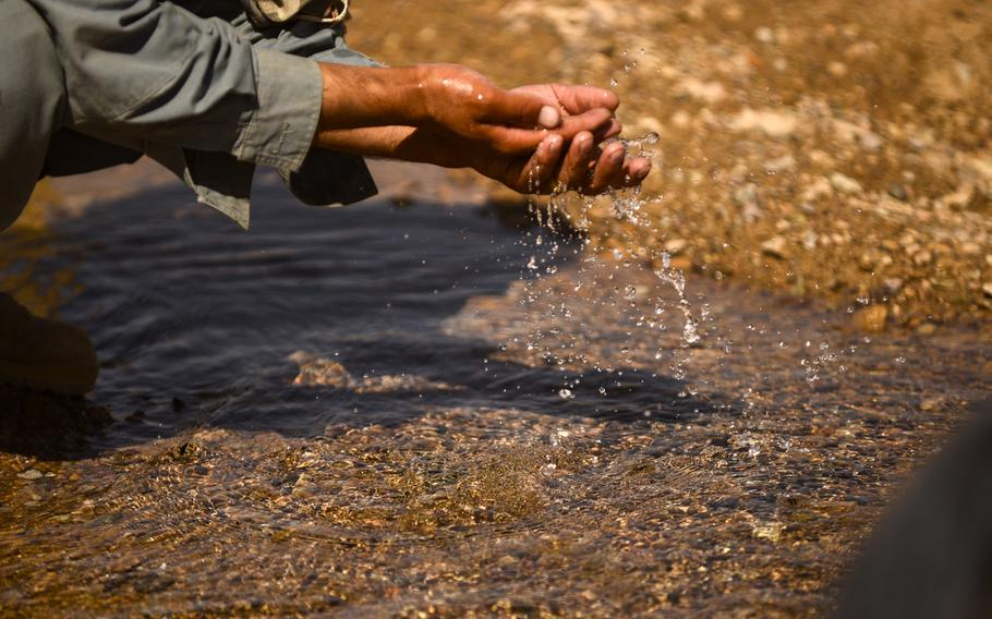 An Afghan police member washes his hands in a farmer's well located in the desert of southern Afghanistan's Zhari district on Oct. 21, 2013.