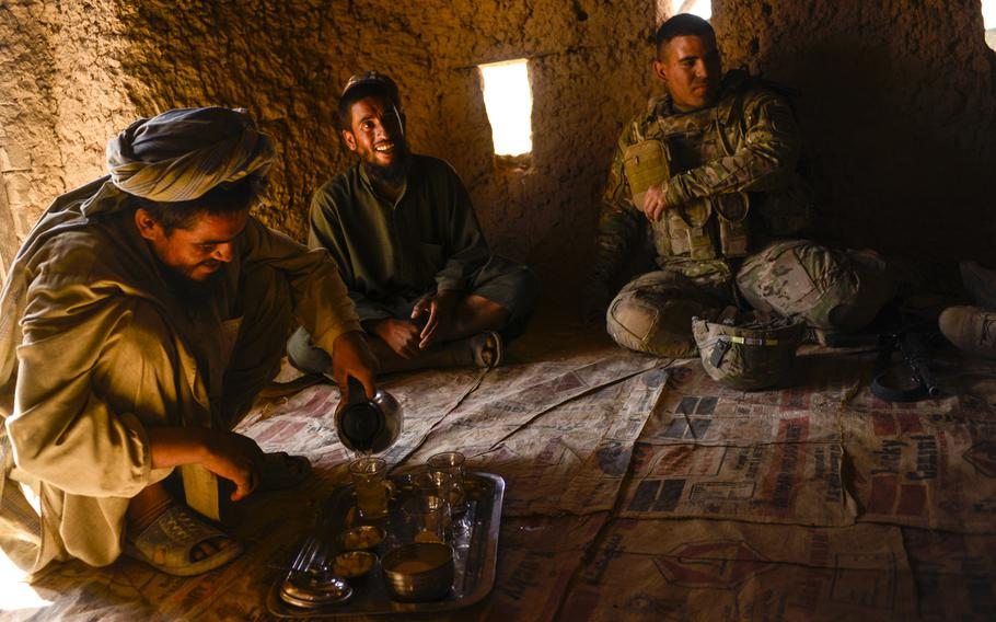 Soldiers with the 2nd Cavalry Regiment, the 163rd Military Intelligence Battalion, along with Afghan police, drink chai with farmers in the desert of southern Afghanistan's Kandahar province just north of Forward Operating Base Pasab on Oct. 21, 2013.