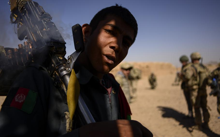 An Afghan policeman smokes hashish during a partnered patrol with 3rd Squadron, 2nd Cavalry Regiment just north of Forward Operating Base Pasab located in southern Aghanistan's Zhari district on Oct. 21, 2013.