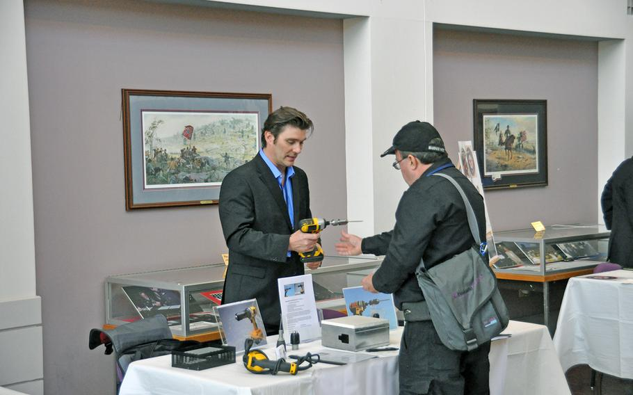 """Army veteran Walter Nagel III shows off his """"SHUR-A-TAK"""" universal screw attachment to a potential investor at the Veterans Venture Forum event on Oct. 29. The event paired veteran entrepreneurs with individuals and firms looking to invest in new start-ups."""