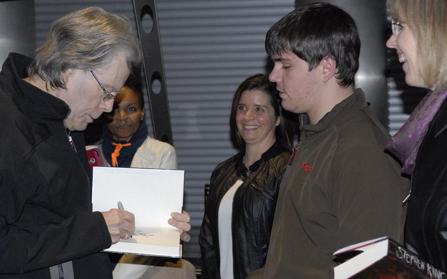 """Stephen King, American author of contemporary horror, suspense, science fiction and fantasy, signs a copy of his new book, """"Doctor Sleep,"""" for Andrew Bolton and his mom, Laura, right, prior to his book reading at Ramstein Air Base, Germany, on Monday, Nov. 18, 2013. The Boltons won tickets to the limited-seating event in an American Forces Network contest."""