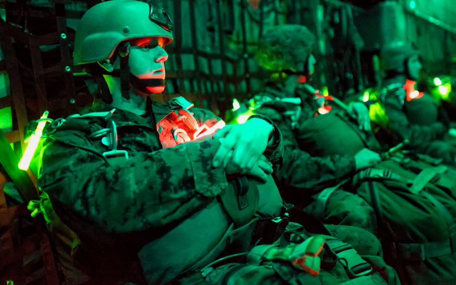 Marines with the 3rd Reconnaissance Battalion, 3rd Marine Division, wait on a C-130 Hercules prior to taking part in night jump training over Yokota Air Base, Japan, Nov. 21, 2013. The training not only allowed the Marines to practice jumping, but it also allowed the Yokota aircrews to practice flight tactics and timed-package drops.