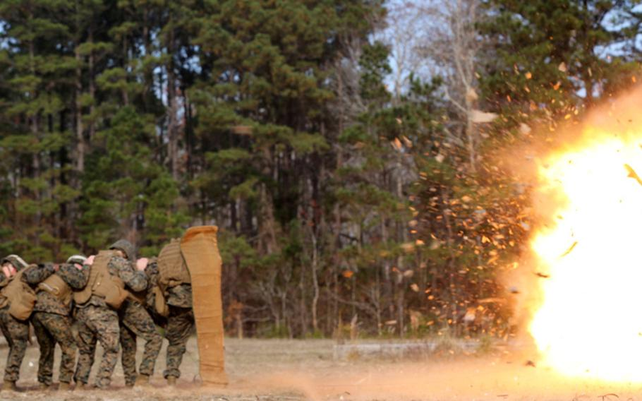 Marines and sailors with Marine Wing Support Squadron 271 take cover behind a blast blanket on Dec. 3, 2013, during annual demolition training at Marine Corps Air Station Cherry Point's Explosive Ordnance Disposal range in North Carolina.