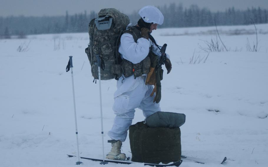 Staff Sgt. Bruce Henderson, an infantryman with 4th Infantry Brigade Combat Team (Airborne), 25th Infantry Division, secures his equipment in preparation to move after jumping from a C-130 Hercules on Dec. 12, 2013 at the Malemute Drop Zone at Joint Base Elmendorf-Richardson, Alaska. Henderson said the jump gave soldiers a chance to familiarize themselves with carrying arctic equipment while jumping from an aircraft.