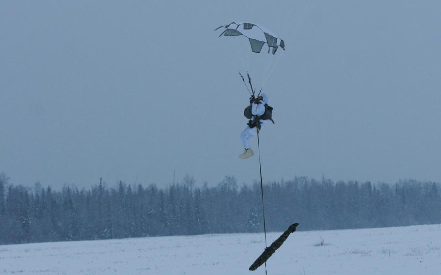 A paratrooper with the 4th Infantry Brigade Combat Team (Airborne), 25th Infantry Division, prepares to land at the Malemute Drop Zone at Joint Base Elmendorf-Richardson, Alaska after jumping from a C-130 Hercules.