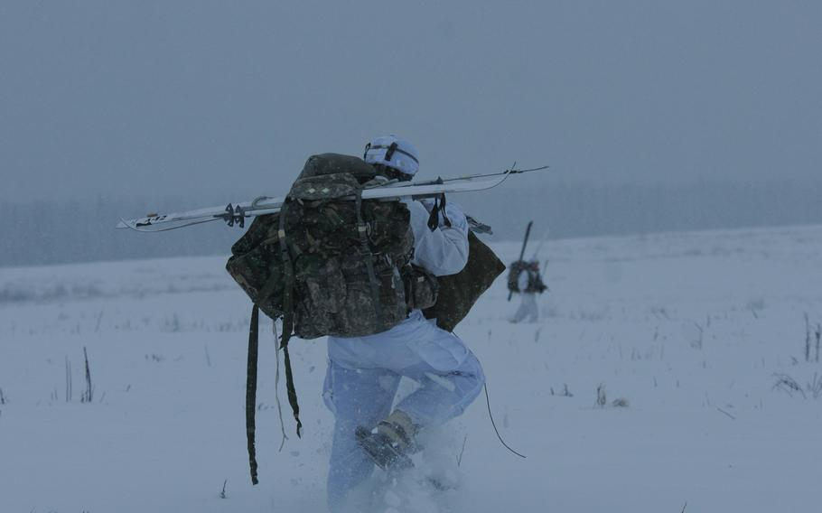 A paratrooper with the 4th Infantry Brigade Combat Team (Airborne), 25th Infantry Division, moves off the drop zone carrying skis on Dec. 12, 2013 at the Malemute Drop Zone at Joint Base Elmendorf-Richardson, Alaska. According to one soldier, the jump was a chance to test jumping from the plane with skis.