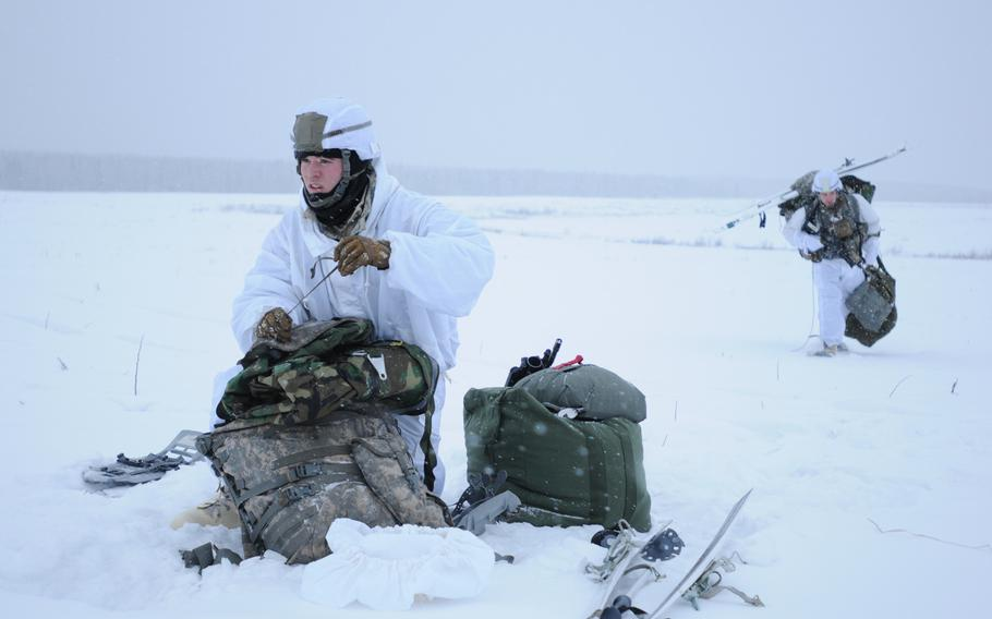 Spc. William Baker, left, an infantryman with 4th Infantry Brigade Combat Team (Airborne), 25th Infantry Division, secures his equipment in preparation to move after jumping from a C-130 Hercules on Dec. 12, 2013 at the Malemute Drop Zone at Joint Base Elmendorf-Richardson, Alaska.