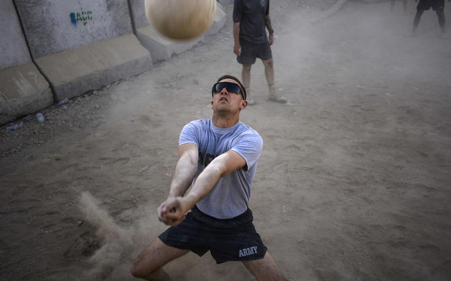 First Lt. Jeremy Kinder, a platoon leader with 1st Squadron, 2nd Cavalry Regiment, attempts to save a volleyball that went deep during an Oct. 3, 2013, match at the new volleyball court at Forward Operating Base Zangabad, Afghanistan. The court was recently knicknamed the ''dust bowl.''