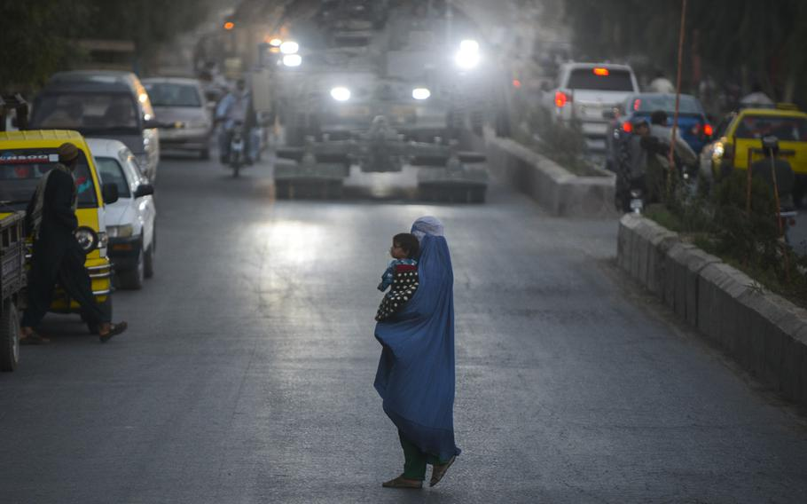 A burqa-clad woman carries a child amid the traffic of a busy Kandahar City street as L Troop, 2nd Cavalry Regiment, provides security for a unit of engineers sweeping nearby roads for bombs on Oct. 10, 2013, in Afghanistan.