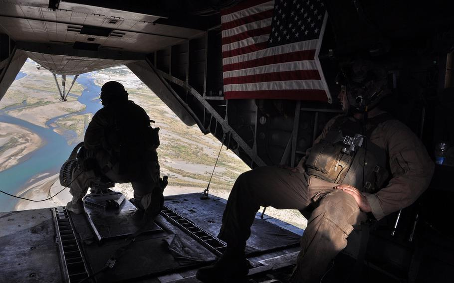Sgt. Caleb Dye, left, and Sgt. Travis Eideh scan the landscape from the back of a helicopter flying out of Forward Operating Base Jackson, Afghanistan, in May 2013. The desert below, Sangin district, had become a symbol and a flash point for the insurgents, Afghan government and NATO coalition forces.