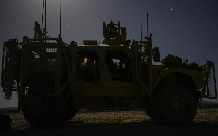 Staff Sgt. Shayne Laflin, with the 3rd Brigade, 1st Infantry Division, looks at photographs of his 7-month-old daughter on an iPhone inside an MRAP all-terrain vehicle at what used to be Forward Operating Base Sweeney in a remote corner of southern Afghanistan's Zabul province.