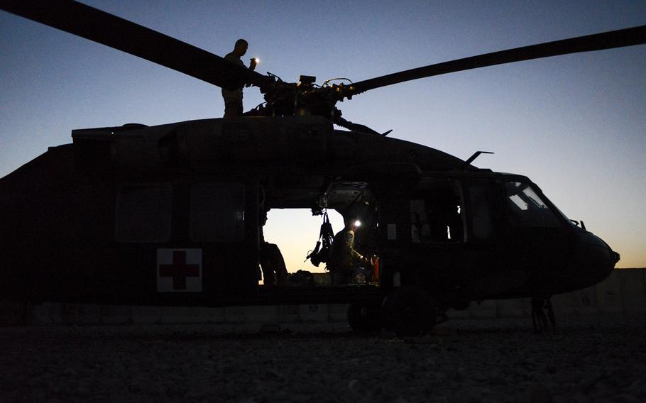 Crewmembers from 4th Platoon, Company C, out of Fort Riley, Kan., conduct post-flight maintenance checks on the helipad of Forward Operating Base Pasab, Afghanistan, after completing a medical evacuation mission on Oct. 22, 2013.