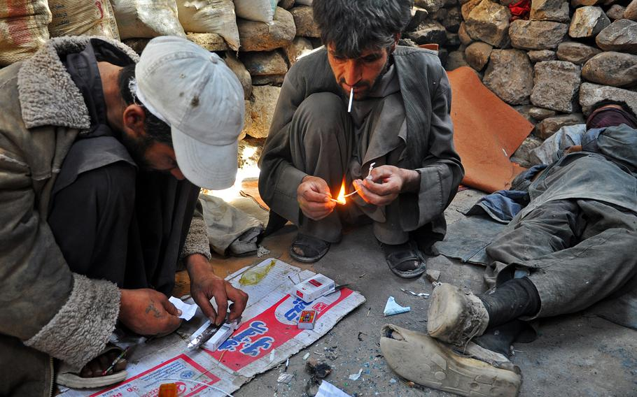 Men prepare heroin in Dahne Kamarkalagh, a colony of drug addicts on the outskirts of Herat, a city in western Afghanistan. Though Herat has been more prosperous and peaceful than much of the rest of the country, it has an estimated 60,000 to 70,000 drug addicts, most hooked on heroin and other opiates.
