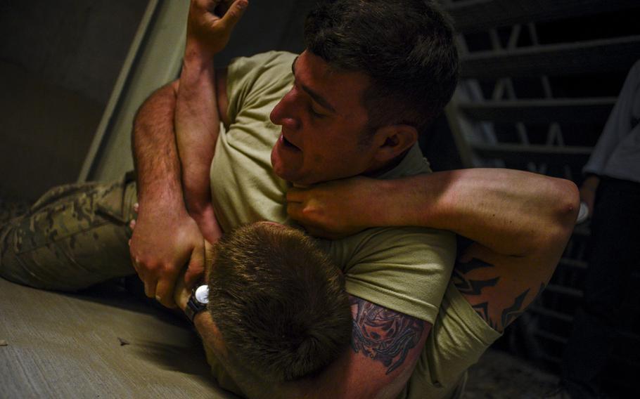 Pfc. Jeremy Monteleone, top, wrestles with Spc. Joshua Jarosz outside their rooms on Kandahar Airfield on Oct. 13, 2013.