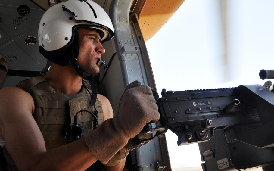 Sgt. Mohammed Shafi scans for threats from the door of an Afghan air force Mi-17 helicopter during a training mission in Uruzgan province in southern Afghanistan.