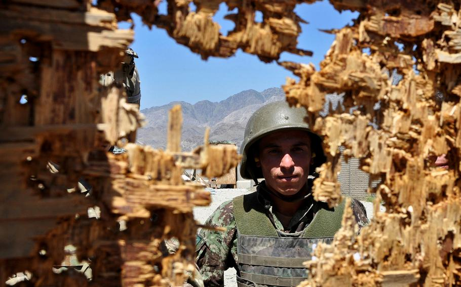 Afghan National Army soldier Mohammed Haroon examines his target during rifle training at Forward Operating Base Joyce in eastern Afghanistan. U.S. advisers sought to teach Haroon and other Afghan soldiers how to train other soldiers on a rifle range.