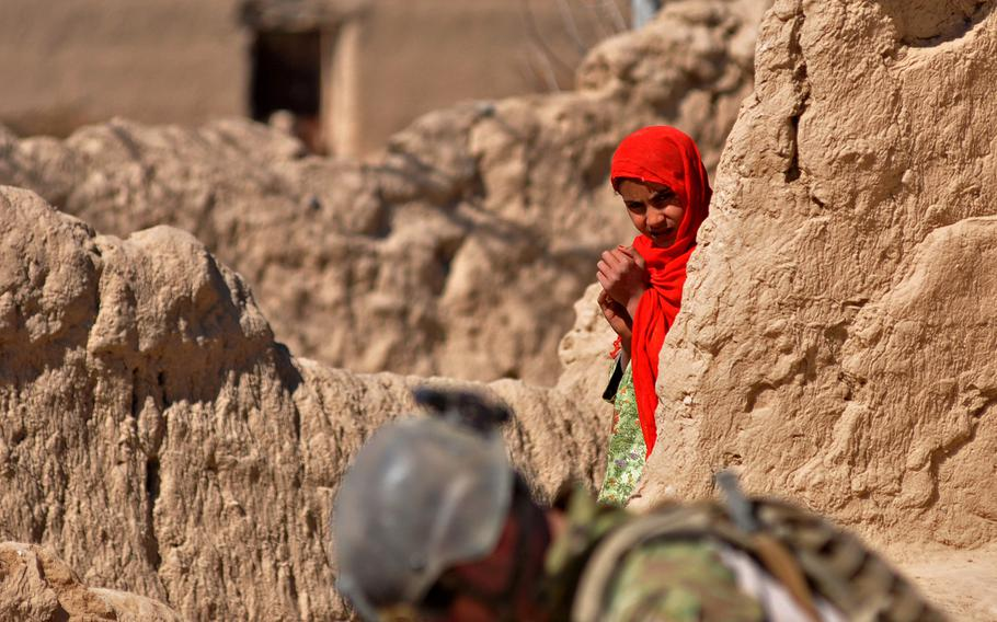 An Afghan girl watches U.S. Army Psychological Operations soldiers unpack gear during a patrol in a village near Forward Operating Base Zangabad, in Kandahar province.