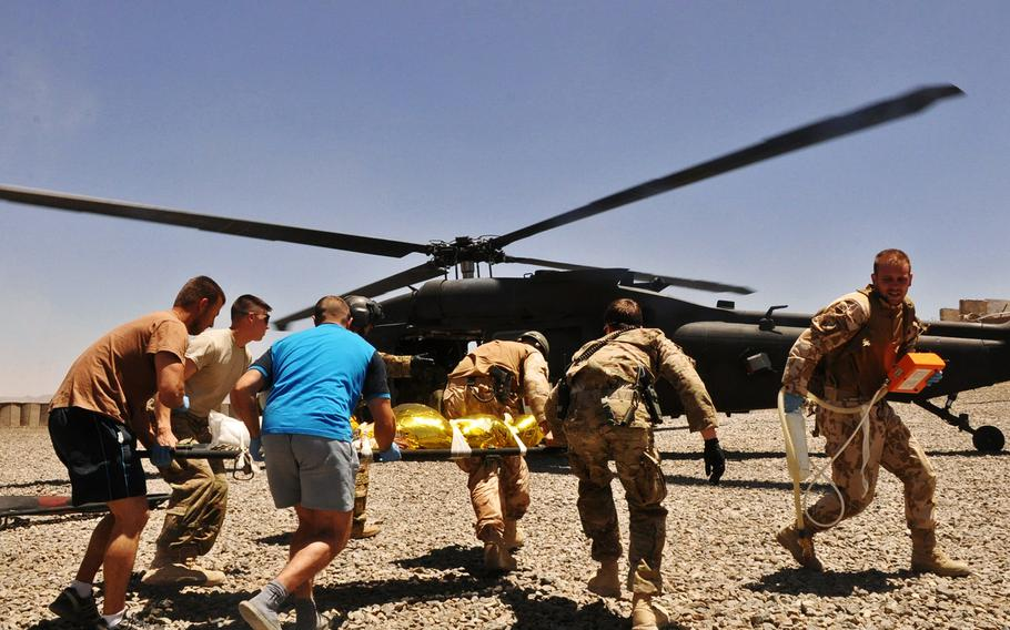 U.S. and Czech medics rush a young Afghan boy to a Black Hawk helicopter for evacuation after he was shot in the back of the head by a ricochet bullet on a firing range at Combat Outpost Soltan Kheyl in July 2013. The boy was said to have been collecting empty bullet cases when he was hit.