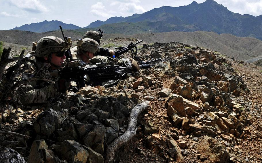 From left, Sgt. Joshua Sutherland, 1st Lt. James Kromhout, and Pfc. Alex Bolden set up a blocking position to provide security while Afghan forces search a village in Khost province in August 2013.