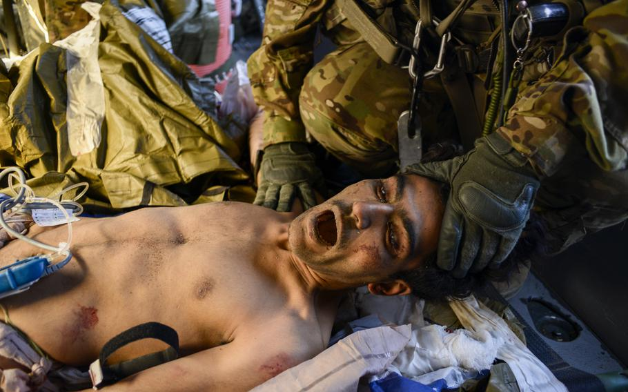 An Afghan soldier who has just lost both legs from a roadside bomb is restrained by Sgt. James Bell, a crew chief, during a medical evacuation flight, Oct. 22, 2013. Even crew chiefs are used during such missions, as space is tight and the more hands available for care, the better.