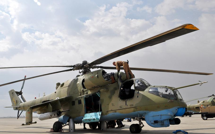 Czech air force 1st Lt. Miroslav Berger checks an Afghan air force Mi-35 attack helicopter before a training flight at Kabul in July 2013. NATO advisers still often fly with Afghan pilots.