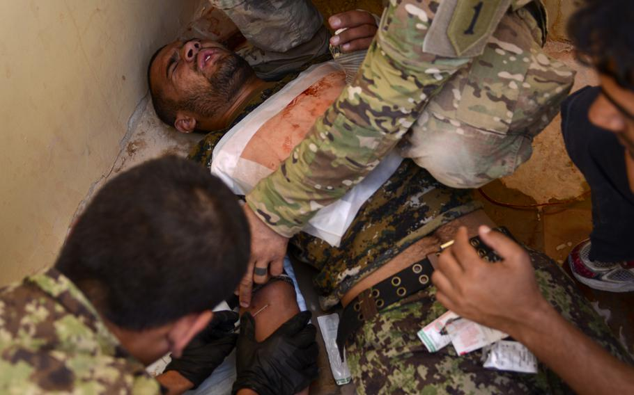 An Afghan National Army soldier grimaces as he receives an intravenous ''stick'' while role-playing as a casualty in a medic training exercise on Forward Operating Base Eagle, Afghanistan, on Sept. 19, 2013.