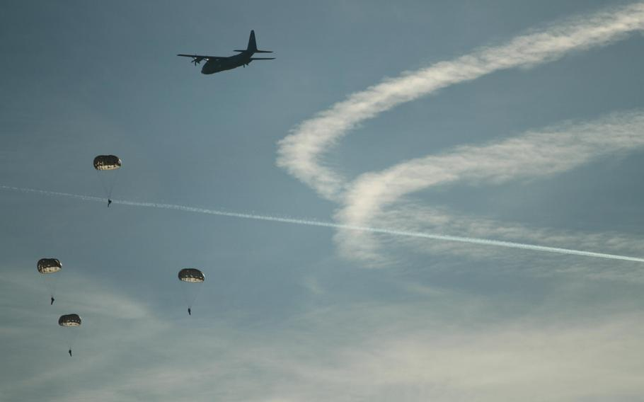 U.S. and European military personnel parachuted to the ground as a U.S. Air Force C-130 flies by Monday, Dec. 16, 2013, the first day of International Jump Week.
