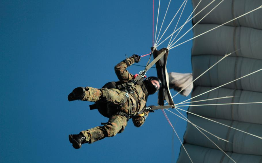 A German soldier maneuvers over a landing zone outside the town of Alzey during a multinational parachute jump Monday, Dec. 16, 2013. The International Jump Week event included a jump by Santa Claus and an air drop of holiday gifts.