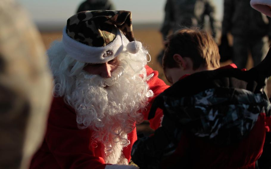 Santa Claus hands out candy and presents to the children of U.S. service members after parachuting from a U.S. Air Force C-130 transport plane Monday, Dec. 16, 2013, near the town of Alzey, Germany.