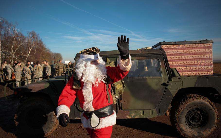 Santa Claus waves to children and members of the military after parachuting from a C-130 military transport Monday, Dec. 16, 2013, near the German town of Alzey.