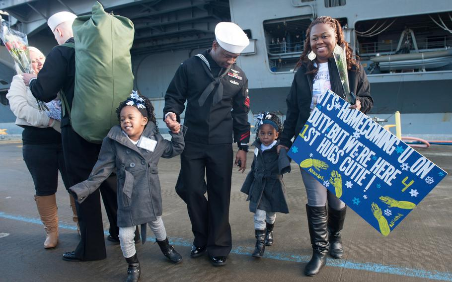 Petty Officer 1st Class Quindric Woods, center, from Baton Rouge, La., reunites with his family after the aircraft carrier USS Nimitz arrives at homeport at Naval Station Everett, Wash., on Dec. 16, 2013.