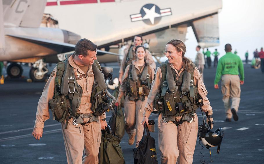 """Capt. Sara Joyner, commander, Carrier Air Wing 3, of Hoopers Island, Md.; and Lt. Cmdr. Eddy DePuy, of Tallahassee, Fla., leave an E-2C Hawkeye, assigned to the """"Seahawks"""" of Airborne Early Warning Squadron 126, on the flight deck of the aircraft carrier USS Harry S. Truman while sailing the Gulf of Oman Dec. 14, 2013."""